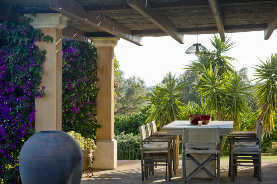 Lunch in the patio with a view of the pool surrounded by greenery in Villa Bouganville Castelvetrano Scent of Sicily