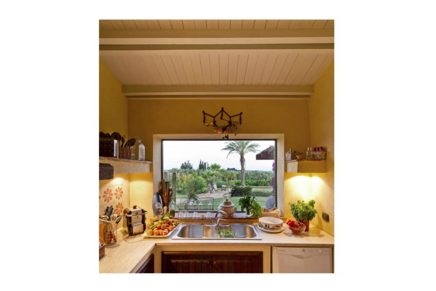 The view of the beautiful garden from the equipped kitchen in Villa Bouganville Castelvetrano Scent of Sicily
