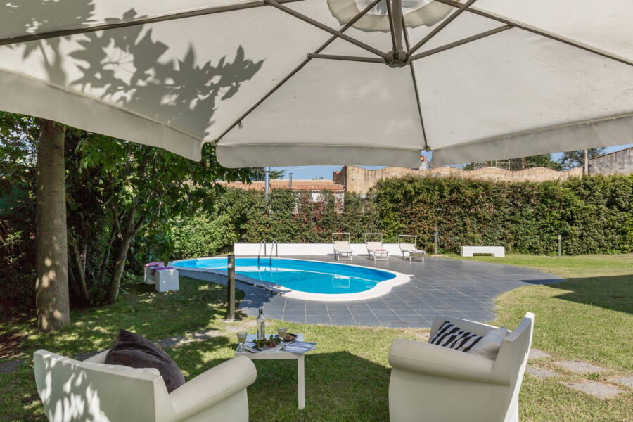 Sitting in the garden in the shade of a sun umbrella with a view of the swimming pool.