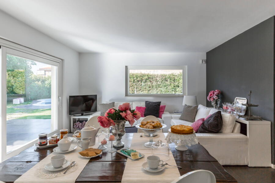 The dining table between the kitchen and the TV area, which overlooks the veranda through a wide glass window.