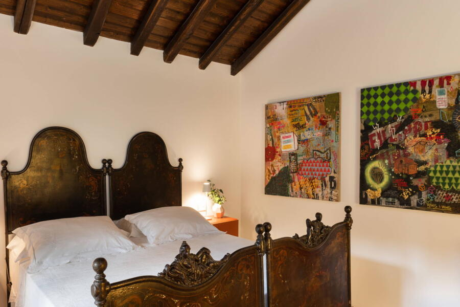 The loft is another space in the villa where the bed in traditional style blends harmoniously with modern art