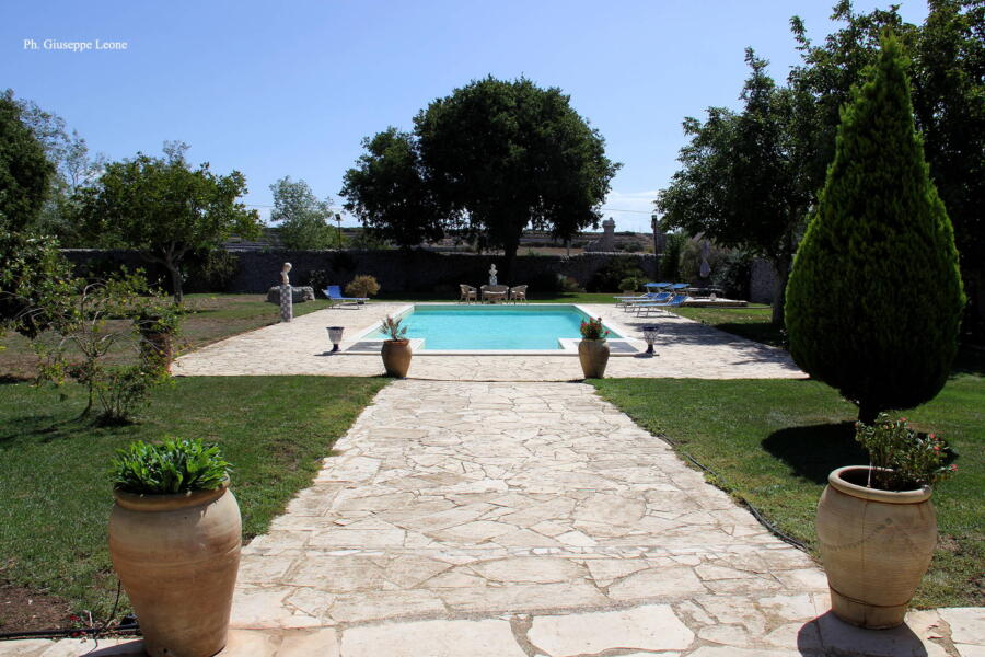 The greenery of this charming historic residence surrounds the swimming pool.