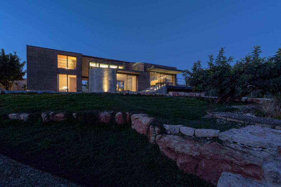 The evening lights highlight the refined structure of the villa