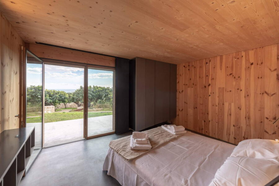 The neutral materials used in the bedroom and the nature that can be seen through the large windows.