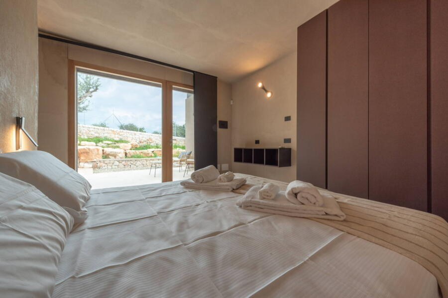 The double bedroom overlooks its veranda surrounded by nature that can be seen through the large windows.