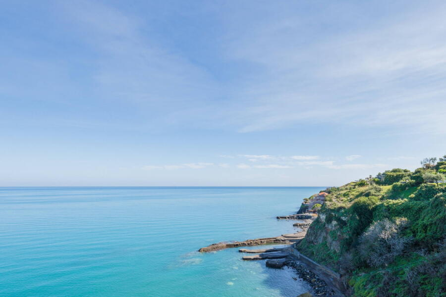 The blue sea below the residence which is accessed by a private road, an area which only residents of the residence can access.