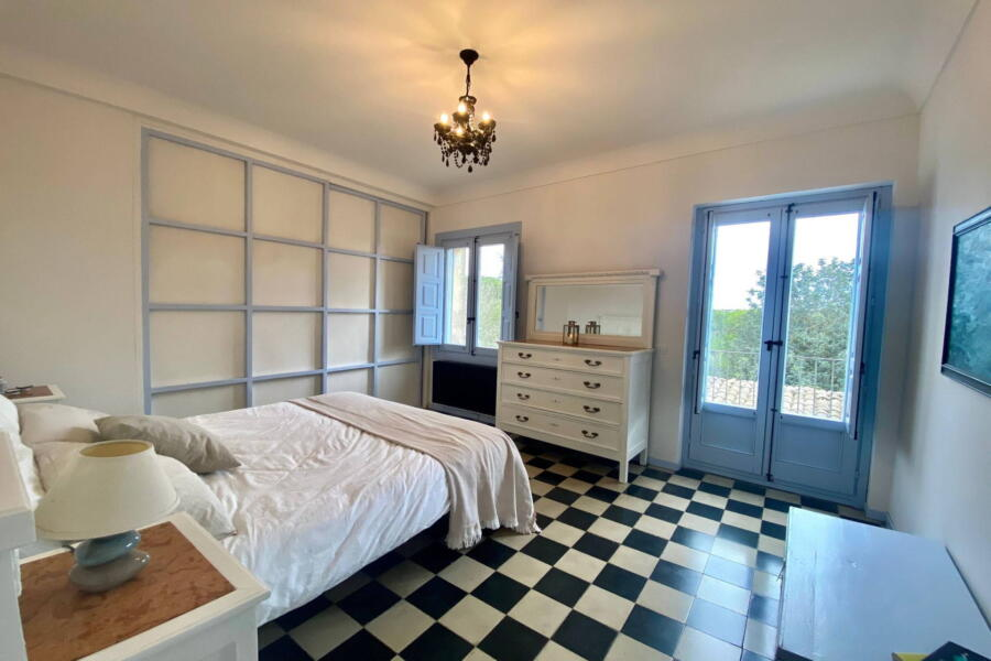 The bedroom on the first floor where blue and white are the predominant colours with a chequered floor.