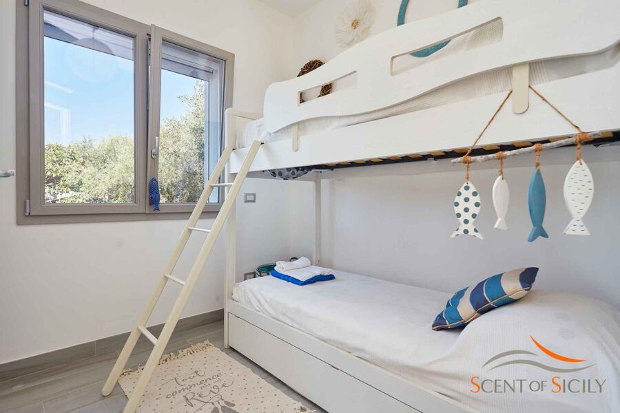 Good night in the room with the white bunk bed with some blue details for a perfect sleep.